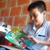 Elkin bladrer i LæseRaketten med historien om ham selv. Hans forældre er stolte af historien. Foto: Laura Victoria Gomez Correa