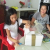 Thaliana og hendes mor åbner kassen. Den er fuld af breve fra børn i Danmark. Foto: Laura Victoria Gomez Correa