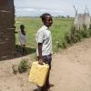 Det er Businges arbejde at hente vand. Hver dag tager han turen til landsbyens hjemmelavede brønd. Turen til brønden er cirka 3 kilometer. Vandet fragter han hjem på hovedet eller i hænderne. - Foto: Heidi Brehm