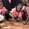 Joshua elsker at spille kalikua. Han er god til det. Snurretoppen hopper ned fra hånden og snurrer videre på jorden. - Foto: Emmanuel Museruka