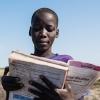 En dreng kigger lige en ekstra gang i sin skolebog, inden han når frem til skolen. Bogen handler om samfungsfag. Foto: William Vest-Lillesøe