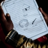 En dreng har lavet små tegninger i sit hæfte og skrevet ordene på sit lokale sprog.  Foto: Pernille Bærendtsen