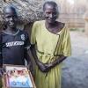 James sammen med sin bedstemor - de står foran deres hytte med et foto af hans far og bror - foto: William Vest-Lillesøe