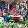 På markedet i Aweil kan man købe mange slags grønt. Her sidder Ngor og Chan sammen med deres tante. - foto: William Vest-Lillesøe