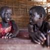 Rhoda og hendes gode veninde, som også hedder Rhoda. De sidder på bænken i et klasselokale på deres skole, St. Andrea Primary School - foto: William Vest-Lillesøe