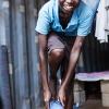Samuel er ved at tage sine flotte blå fodboldstøvler på - dem har han lige fået af sin far - foto: William Vest-Lillesøe